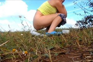 Girl scat on the field with daisies