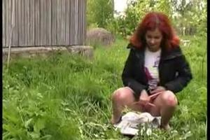 Redhead chick pissing on a newspaper