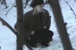 Strange girl pissing in the bushes in winter