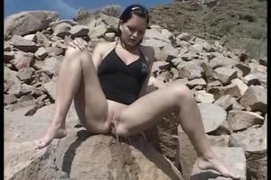 Girl pisses on the rocks