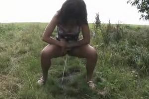 Beautiful girl pissing on the grass