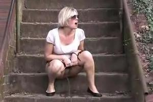 Girl with shaved pussy pissing on the stairs