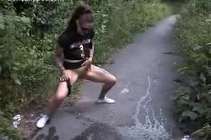 Crazy girl friend pissing on the path between the bushes