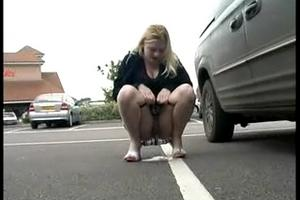 Girl pee near the car in the parking lot