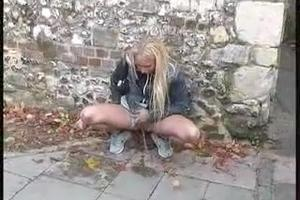 Blonde pissing on the street during the day