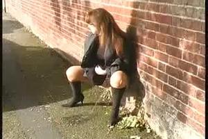 Woman in boots pissing in the street