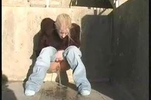 Blonde pissing on the doorstep by the sea